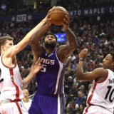 Sacramento Kings centre DeMarcus Cousins (15) is fouled on his way to the net by Toronto Raptors centre Jakob Poeltl (42) as Toronto Raptors guard DeMar DeRozan (10) looks on during first half NBA basketball action in Toronto on Sunday, Nov. 6, 2016. (Frank Gunn/The Canadian Press via AP)